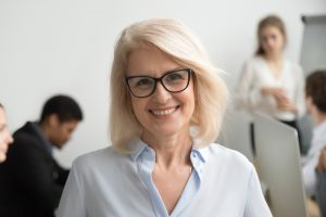 Smiling senior businesswoman wearing glasses portrait with busin